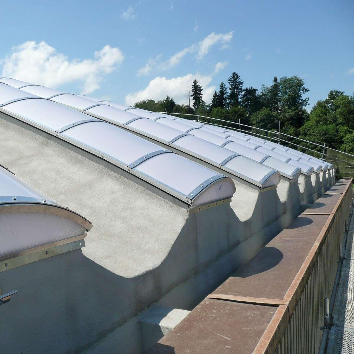 Steeltec AG   Emmenbrücke, İsviçre • Kavisli beton prekast üzerine monte edilmiş kontinü çatı ışıklıkları.